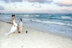 Caribbean Beach Wedding - Garter Belt. Groom removing the brides garter belt on the beach stock photos