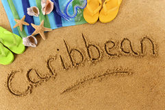Caribbean beach writing. The word Caribbean written on a sandy beach, with scuba mask, beach towel, starfish and flip flops Stock Photo