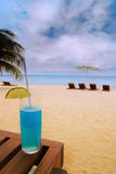 Caribbean cocktail. A blue drinks stands against a caribbean beach Stock Image