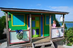 Caribbean Colours. The girl standing by the wooden house coloured in bright Caribbean colours on Half Moon Cay, The Bahamas stock photo