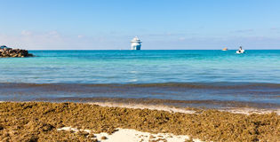 Caribbean. Cruise ship anchores in the Caribbean Sea while tendering passengers to remote tropical island Stock Images