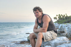 Caribbean dream. Handsome fit Caucasian man sits on rocky Caribbean shore enjoying peace and relaxation of solitude in nature Royalty Free Stock Photo