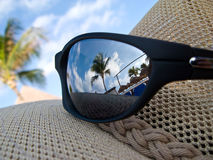 Caribbean glasses. Sun glasses on hat with a caribbean background royalty free stock image