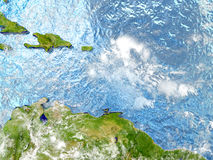Caribbean on map with clouds. Caribbean in red on map with detailed landmass texture, realistic watery oceans and clouds above the surface. 3D illustration Royalty Free Stock Image