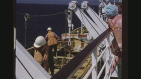 Inspecting The Rescue Boats. CARIBBEAN, MAY 1971. Two Shot Sequence Of Crew Members In Lifevests Inspecting The Rescueboats On The Russian Cruise Liner Taras stock video footage