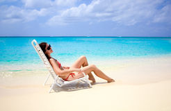 Caribbean paradise. Young woman relaxing in a beach chair on the edge of the blue caribbean waters Stock Image