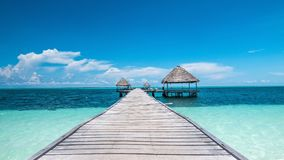 Caribbean paradise found in Cuba: walking dock and houses in the middle of the sea. This beautiful wooden dock is found in Cayo Gulliermo, a beautiful atoll in Royalty Free Stock Photo