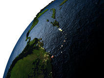 Caribbean in red on Earth at night. Caribbean highlighted in red on planet Earth with visible city lights. 3D illutration with detailed planet surface. Elements Stock Photo