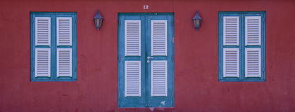 Caribbean Red #12. Green windos with white shutters on a read wall in the caribbean with the number 12 above the door royalty free stock photo