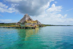 Caribbean resort with thatched bungalow over water Stock Images