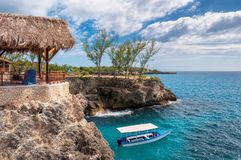 Caribbean rocky beach with turquoise water, tourists boat and lighthouse in Negril Jamaica. Beautiful turquoise water on Caribbean paradise island Royalty Free Stock Photo