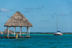 Caribbean scene with hut and Sailboat. Bacalar, near tulum. Trav Royalty Free Stock Images