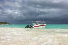Caribbean sea before the rain. Boat with two people moored at the shore. Clouds. Turquoise water royalty free stock images