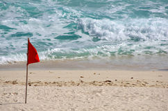 Caribbean sea. Red warning flag on the beach, Cancun, Mexico Stock Images