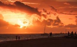 Caribbean seascape at sunrise. Atlantic ocean. Coast, ordinary people walking on sandy beach in red morning sunlight Stock Photography