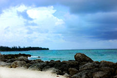 Caribbean Shoreline. Peaceful escape depicted by the crisp blue water hitting a rocky yet sandy shoreline Stock Photos