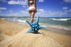 Caribbean starfish over wavy sand beach and beautiful woman Stock Photo