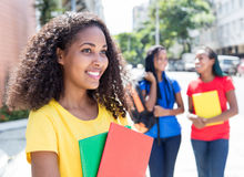 Caribbean student looking sideways in the city with friends. With modern buildings in the background Royalty Free Stock Images