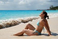 Caribbean Sunbath. The girl having a sunbath on Half Moon Cay beach, The Bahamas royalty free stock photography