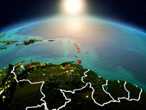 Caribbean in sunrise from orbit. Sunrise above Caribbean highlighted in red on model of planet Earth in space with visible country borders. 3D illustration royalty free stock images
