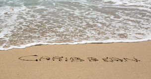 Caribbean written in sand with sea surf Royalty Free Stock Photography