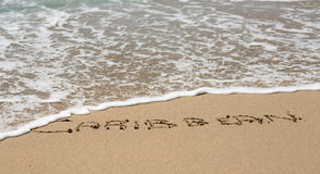Caribbean written in sand with sea surf Stock Photo