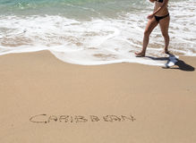 Caribbean written in sand with sea surf Stock Photos