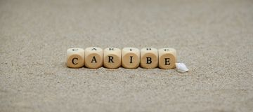 Caribe word built with wooden cubes and black letters on the floor and bottom of sand beach. Advertising art background brand card commercial concept customer stock photos
