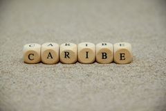 Caribe word built with wooden cubes and black letters on the floor and bottom of sand beach. Advertising art background brand card commercial concept customer stock photography