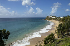 The Caribs. Antigua. The tops of the mountains shining through the emerald green tropical foliage, snow-white and Golden beaches, quiet lagoons and bays which Royalty Free Stock Image