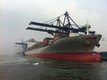 Caricando e scaricando contenitore al porto di Tanjung Priok con le gru del contenitore Fotografia Stock Libera da Diritti