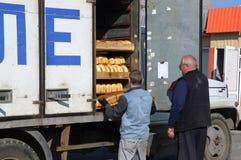 Caricare i prodotti dal furgone del pane del forno Fotografia Stock