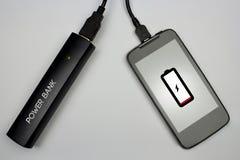Caricare la batteria del cellulare con la banca di potere Immagini Stock Libere da Diritti
