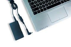 Caricatore del cavo di alimentazione dell'adattatore del computer portatile sul pavimento bianco fotografie stock