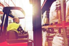 Caricatore di funzionamento del carrello elevatore dell'uomo al magazzino Immagine Stock
