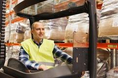 Caricatore di funzionamento sorridente del carrello elevatore dell'uomo al magazzino Immagini Stock