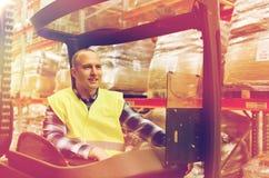Caricatore di funzionamento sorridente del carrello elevatore dell'uomo al magazzino Fotografia Stock Libera da Diritti