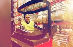 Caricatore di funzionamento sorridente del carrello elevatore dell'uomo al magazzino Immagine Stock