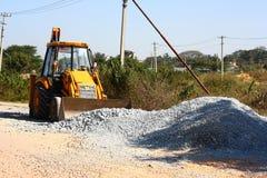 Caricatore giallo dell'escavatore a cucchiaia rovescia nella costruzione di strade Fotografia Stock Libera da Diritti