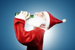 Caricature of funny drunken santa claus drinking beer. In green bottle Stock Images
