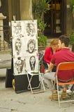 Caricature in Siena. Steet artist in Siena. Man looking at caricature Royalty Free Stock Image