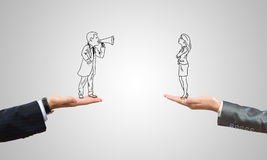 Caricatures of businessman and businesswoman. Drawn businesspeople in human palms on gray background stock photography