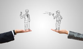 Caricatures of businessman and businesswoman. Drawn businesspeople in human palms on gray background royalty free stock images