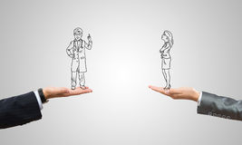Caricatures of businessman and businesswoman. Drawn businesspeople in human palms on gray background Royalty Free Stock Photo