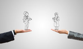 Caricatures of businessman and businesswoman. Drawn businesspeople in human palms on gray background stock images