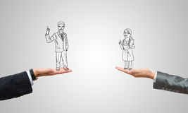 Caricatures of businessman and businesswoman. Drawn businesspeople in human palms on gray background royalty free stock photos