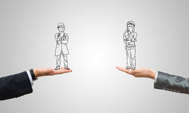 Caricatures of businessman and businesswoman. Drawn businesspeople in human palms on gray background stock photos