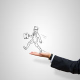 Caricatures of businessman in palm. Drawn businessman with suitcase in male palm on gray background Royalty Free Stock Image