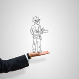 Caricatures of engineer man. Drawn construction man in male palm on gray background stock image