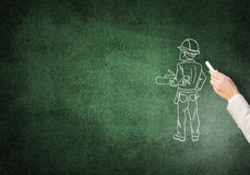 Caricatures of engineer man. Male hand drawning with chalk construction man on blackboard Stock Image